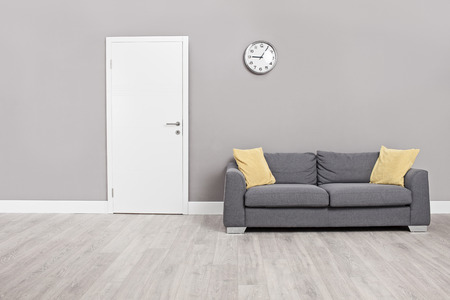 Empty waiting room with a modern gray sofa in front of the door and a clock on the wall