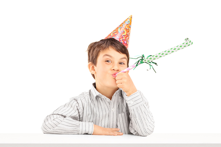 favor: Little kid with party hat sitting at a table and blowing a favor horn isolated on white background Stock Photo