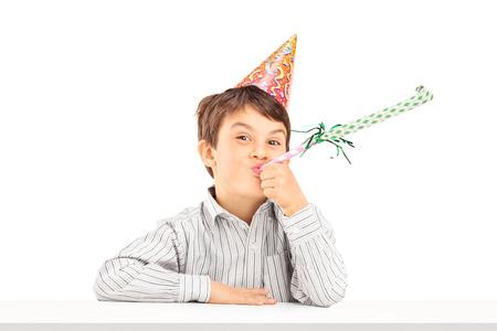 cuernos: Niño con sombrero de fiesta sentado en una mesa y soplando un cuerno favor aislados sobre fondo blanco Foto de archivo