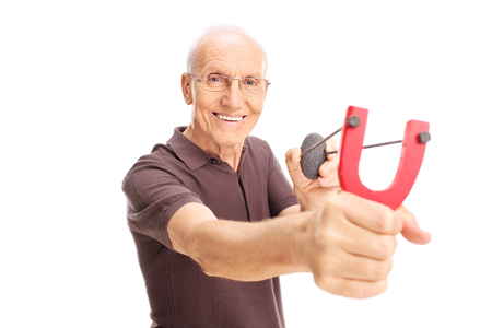 childish: Cheerful senior man shooting a slingshot and looking at the camera isolated on white background Stock Photo