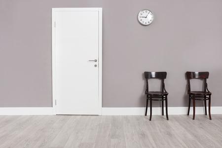 puerta: Dos sillas de madera en una sala de espera con un reloj colgado en la pared por encima de ellos