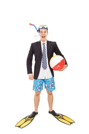 flippers: Retrato de cuerpo entero de un joven hombre de negocios con una máscara de buceo que sostiene una pelota de playa y mirando a la cámara aislada en el fondo blanco