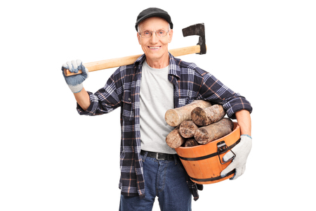shoulder carrying: Senior man carrying an axe over his shoulder and holding basket full of logs isolated on white background Stock Photo