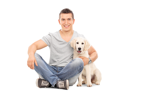 isolated man: Young man sitting on the floor and hugging a Labrador puppy isolated on white background Stock Photo