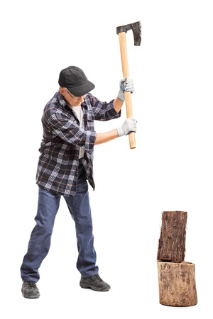 splitting: Full length portrait of a senior man splitting wood with a hand axe isolated on white background