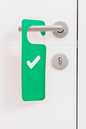 check symbol: Close-up on a metal handle of a white door with a green access plate with check mark on it Stock Photo