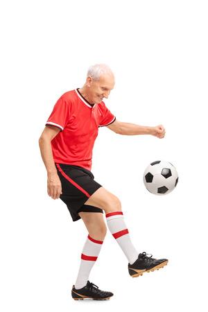 amateur: Retrato de cuerpo entero de un hombre mayor en un jersey rojo malabarismos con un balón de fútbol y sonriente aislados sobre fondo blanco Foto de archivo