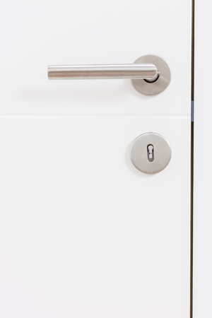 empty keyhole: Vertical studio shot of a gray metal handle on a white door Stock Photo