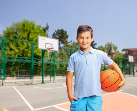 outdoor basketball court: Joyful little boy in a blue shirt holding a basketball at an outdoor basketball court and looking at the camera Stock Photo