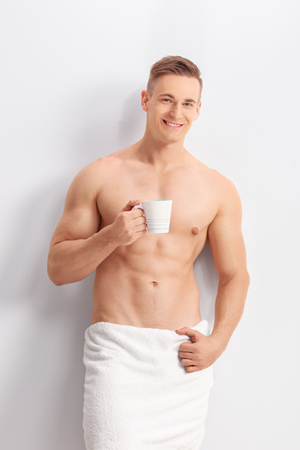 towel: Vertical shot of a handsome man with a white bath towel around his waist holding a cup of coffee and looking at the camera Stock Photo