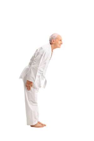 man looking down: Full length profile shot of a senior man in a white kimono bow down isolated on white background