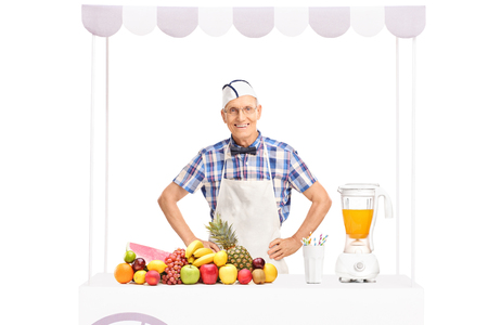 jerk: Mature soda jerk in white apron standing behind a stand full of fresh fruits isolated on white background Stock Photo