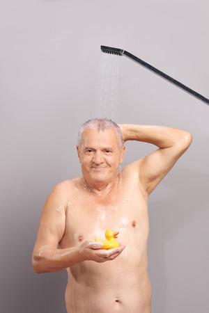 pato de hule: Tiro vertical de un hombre mayor de tomar una ducha y la celebraci�n de un pato de goma amarillo