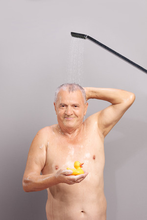 showering: Vertical shot of a senior man taking a shower and holding a yellow rubber duck