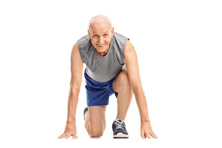 deportistas: Tiro del estudio de un corredor maduro en una posición de partida se prepara para correr y mirando a la cámara aislada en el fondo blanco Foto de archivo