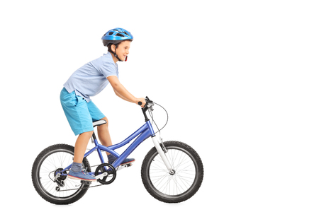 niños en bicicleta: Perfil de disparo de un niño pequeño con el casco azul que monta una pequeña moto azul aislado en fondo blanco