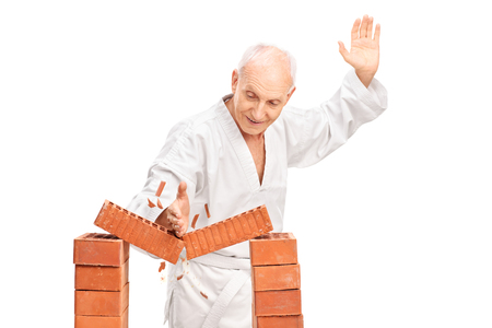 breaking: Studio shot of a senior man in a white kimono breaking a brick with his bare hand isolated on white background