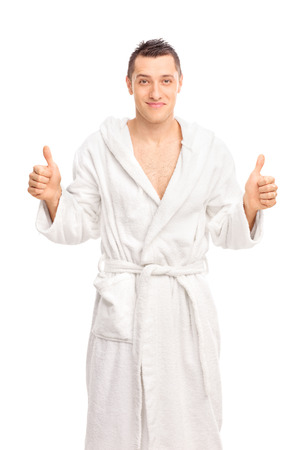 bath robes: Happy young man in a white bathrobe giving two thumbs up and looking at the camera isolated on white background