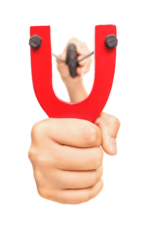 stretched: Hand holding a stretched slingshot with a rock in it isolated on white background Stock Photo