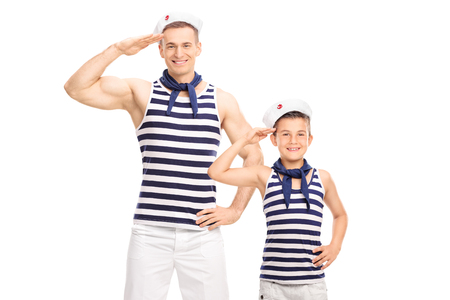 Father and son in sailor uniforms smiling and saluting towards the camera isolated on white background