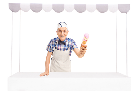 vendors: Senior ice cream vendor standing behind a stall and giving an ice cream towards the camera isolated on white background