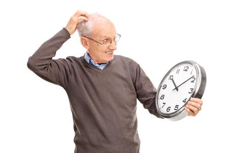 confundido: Confuso que sostiene un reloj de pared principal grande y rasc�ndose la cabeza aislada en el fondo blanco