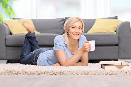 Young blond woman drinking coffee and lying on the floor in front of a gray sofa at home