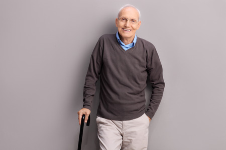 canes: Senior gentleman holding a black cane and leaning against a gray wall