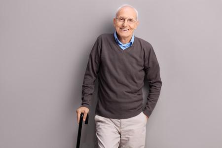 uomo felice: signore anziano in possesso di un bastone nero e appoggiato a un muro grigio Archivio Fotografico