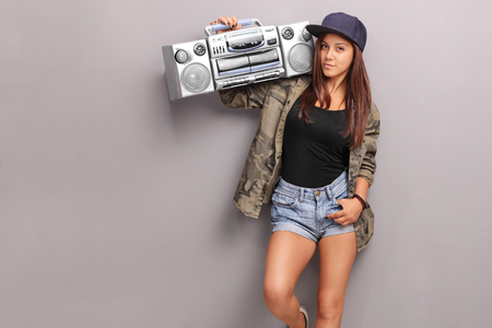 Teenage girl in hip hop clothes holding a ghetto blaster over her shoulder and looking at the camera