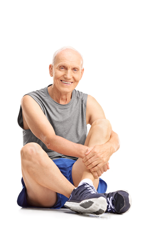old man happy: Active senior man in sportswear sitting on the floor and looking at the camera isolated on white background