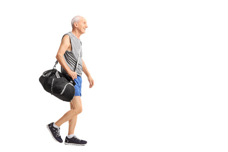 Full length profile shot of a senior man walking and carrying a sports bag isolated on white background