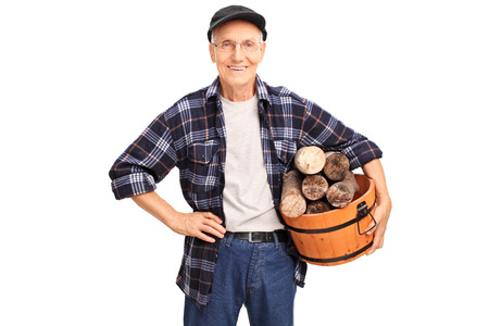 log basket: Cheerful senior in a blue checkered shirt holding a basket full of logs and smiling isolated on white background