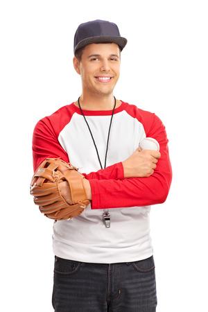 hombre con sombrero: El estudio tiró de un hombre joven con un guante de béisbol de la celebración de una pelota de béisbol y llevaba un silbato alrededor del cuello aislado en el fondo blanco Foto de archivo