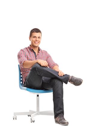 Estudio tiro vertical de un joven relajado sentado en una silla y mirando a la cámara aislada en el fondo blanco