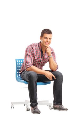 hombre sentado: Tiro vertical de un hombre joven ocasional que se sienta en una silla y mirando a la cámara aislada en el fondo blanco Foto de archivo