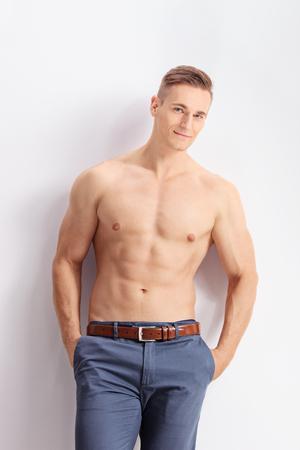 hombre sin camisa: Tiro vertical de un hombre sin camisa guapo apoyado contra una pared y mirando a la cámara