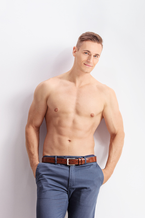 man with camera: Vertical shot of a handsome shirtless man leaning against a wall and looking at the camera