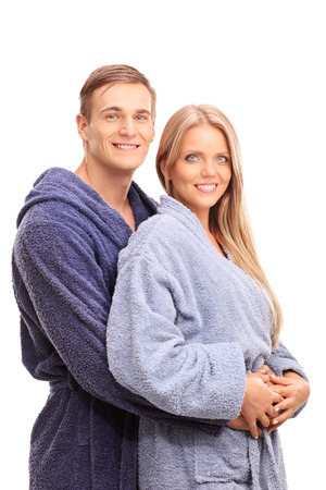 love expression: Young man in a bathrobe hugging his girlfriend and posing together isolated on white background