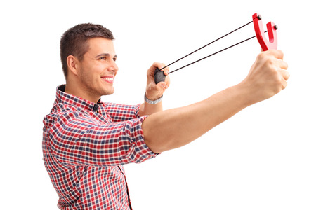 cheerful: Profile shot of a young cheerful man shooting a slingshot and smiling isolated on white background