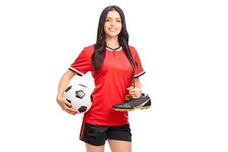uniforme de futbol: Joven jugador de fútbol femenino que sostiene una bola y llevar sus botas de fútbol sobre su hombro aislado en el fondo blanco
