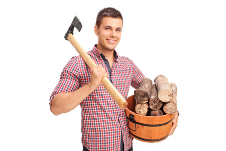 shoulder carrying: Young man carrying an axe over his shoulder and holding a bucket full of logs isolated on white background