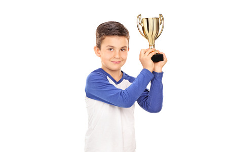 trophies: Studio shot of a cute child holding a golden trophy and looking at the camera isolated on white background Stock Photo