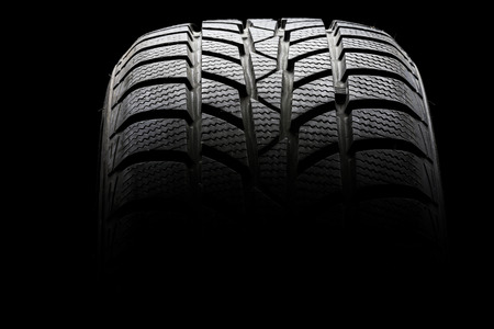 Studio shot of a black car tire in a dark ambient on black background