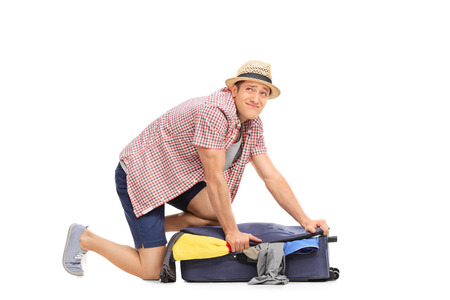 isolated man: Frustrated guy trying to pack a lot of clothes into a single suitcase isolated on white background