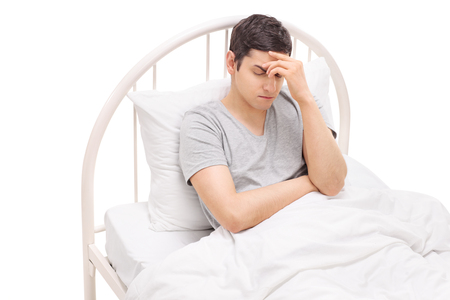 experiencing: Young man lying in bed and experiencing a severe headache isolated on white background