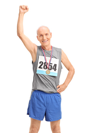 raising: Vertical shot of a mature runner with a medal raising his fist in the air and looking at the camera isolated on white background