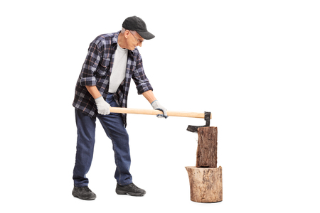splitting: Full length profile shot of a senior splitting wood with an axe isolated on white background