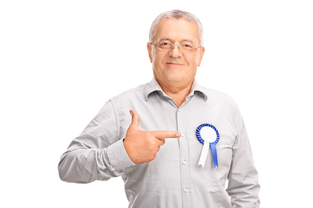 looking towards camera: Mature man pointing towards an award badge on his shirt and looking at the camera isolated on white background Stock Photo