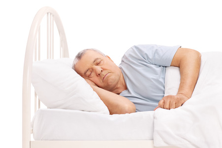 comfortable: Calm senior man sleeping in a bed covered with a white blanket isolated on white background Stock Photo